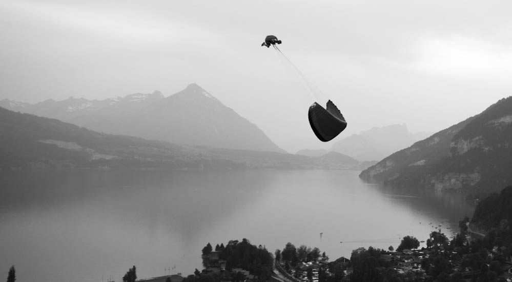 Acro paraglider pilot performing tricks over Interlaken in the evening, Switzerland