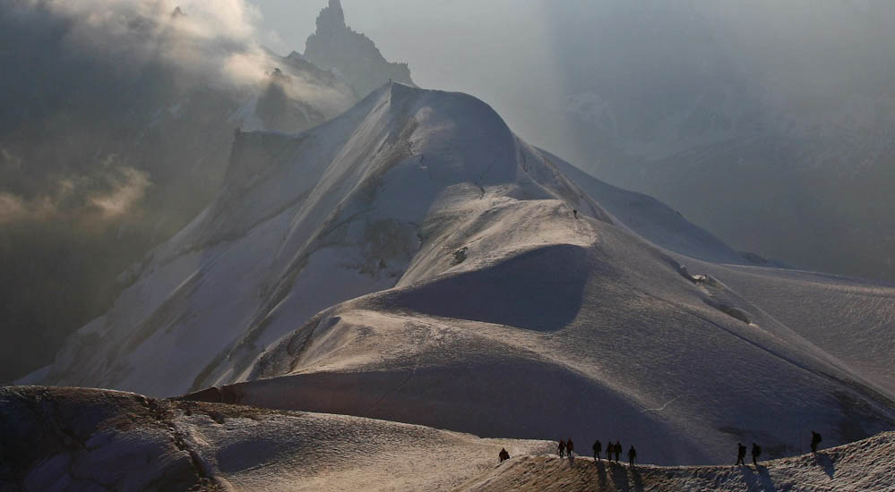 Early morning Alpinists on the Aiguille Du Midi arete (3800m). Chamonix, France